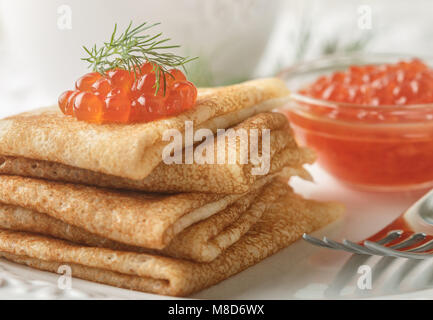 Traditional Russian pancakes (blini ) with salmon caviar on a white plate. Selective focus - Stock Photo