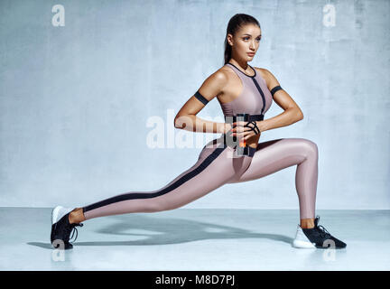 Sporty woman doing lunges with dumbbells. Photo of muscular woman in fashionable sportswear on grey background. - Stock Photo