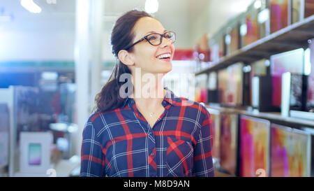 Beautiful Young Woman Walks In the Electronics Store Browsing Shelves with Latest Models of 4K UHD TV's. She Smiles - Stock Photo