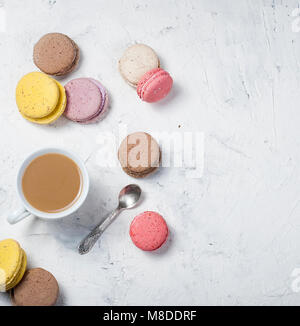 cup of coffee with milk and colorful makaoouns on a light background. Top view. Copy space. - Stock Photo
