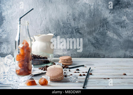 coffee ice in bottle, macaroons,, pieces of chocolate and coffee beans  on a dark  table - Stock Photo