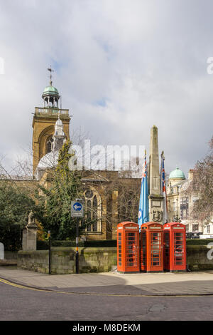 Northampton town centre view with three red telephone boxes in front of a Lutyens designed war memorial, All Saints - Stock Photo