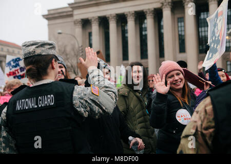 Protestors high five women National Guard members while marching in the Women's March on Washington D.C., January - Stock Photo