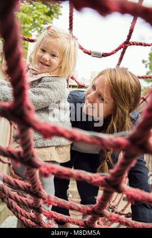 Mother and toddler daughter on playground climbing frame - Stock Photo