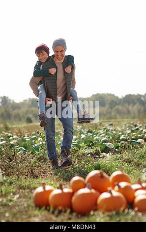 Man giving son piggyback ride in field at pumpkin patch - Stock Photo