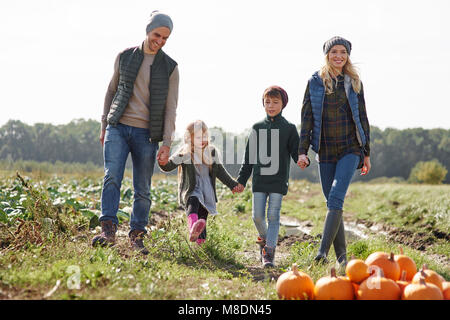 Couple holding hands with son and daughter in pumpkin patch field - Stock Photo