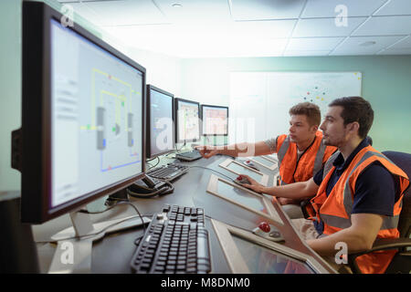 Apprentice engineers in industrial production facility training - Stock Photo
