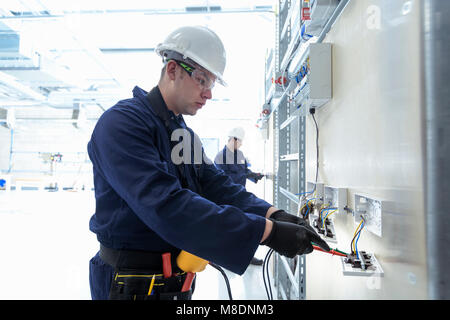 Electrical engineers testing electrical equipment - Stock Photo