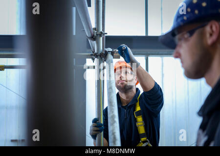 Apprentice engineers preparing and setting up scaffolding - Stock Photo