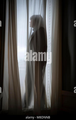 Woman Standing Behind Net Curtain Against Window in Cannes In Provence-Alpes-Côte d'Azur, France - Stock Photo