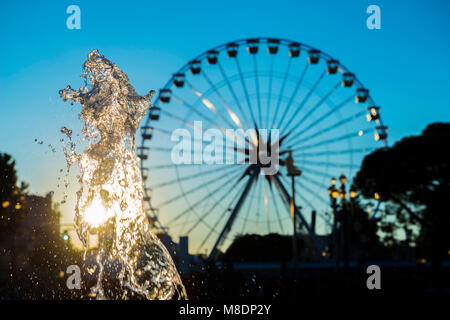 Water Fountain and Ferris Wheel in Sunset in Nice in Provence-Alpes-Côte d'Azur, France - Stock Photo