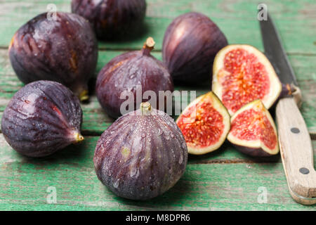 Fresh ripe organic figs with drops of water on a wooden table. Selective focus - Stock Photo