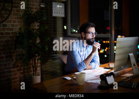 Young businessman looking at computer on office desk at night - Stock Photo