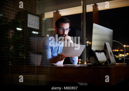 Young businessman reading paperwork at office desk at night - Stock Photo