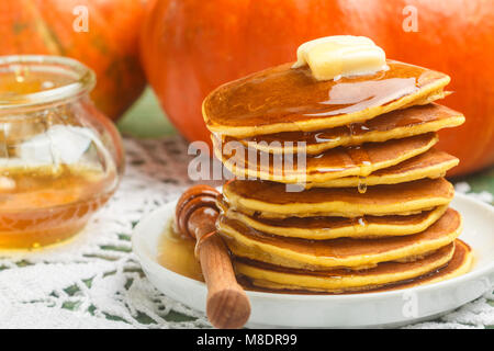 Homemade pumpkin pancakes with butter and honey on a white plate on the table. Useful, tasty Breakfast. Selective - Stock Photo