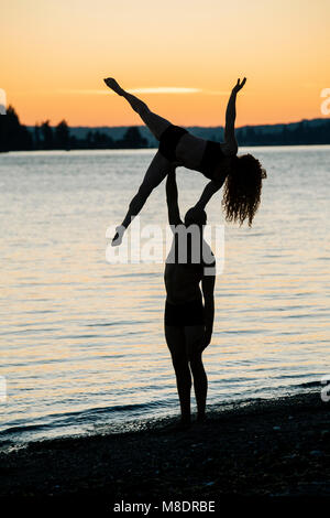 Couple practising yoga on beach at sunset - Stock Photo