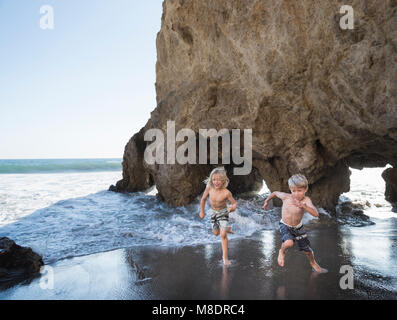 Brothers playing on El Matador Beach, Malibu, USA - Stock Photo
