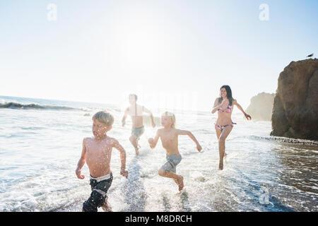 Family playing on El Matador Beach, Malibu, USA - Stock Photo