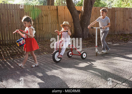 Three children in mini parade, banging drum, riding tricycle and using scooter - Stock Photo