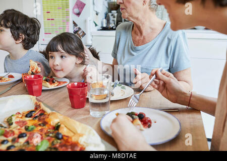 Three generation family sitting at kitchen table eating pizza - Stock Photo
