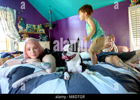 Family and pet dog on bed in bedroom - Stock Photo