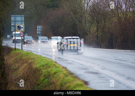 cars driving along water logged road with spray and rain and camera and 50 mph speed warning sign - Stock Photo
