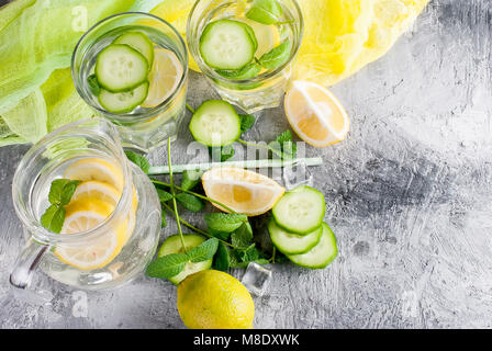 Citrus fruit and herbs infused sassi water for detox, healthy eating in  glasses and jug on over dark background - Stock Photo