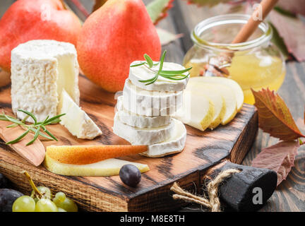 Goat cheese with fruit and honey. Camembert. Bree. Grape, pear and rosemary. Gourmet wine snacks. Selective focus - Stock Photo