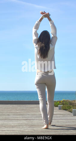 Shot of a Beautiful Brunette with Loose Hair Opening Doors of the Balcony and Walking onto Sunny Terrace with Seaside - Stock Photo