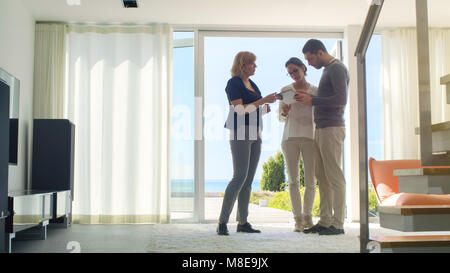 Professional Real Estate Agent Shows Stylish Modern House to a Beautiful Young Couple Who are in the Market for - Stock Photo