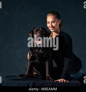 The young woman hugging a mix breed dog - Stock Photo