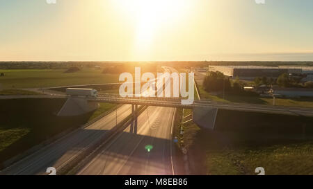 Aerial View of White Semi Truck with Cargo Trailer Passing Highway Overpass/ Bridge. Eighteen Wheeler is New, Loading - Stock Photo