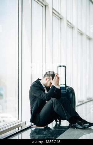 Business man sitting at the terminal airport on the floor with suitcase flight delay, two hands touch at head, headache, - Stock Photo