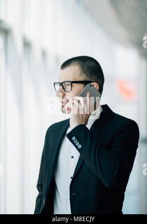 Mature business man standing inside office building and using cell phone. Man standing by window and talking on - Stock Photo