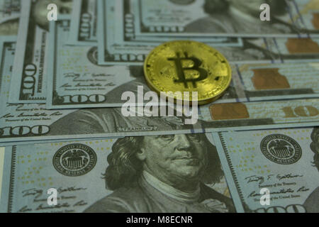 Gold and copper Bitcoin coins and silver litecoin and 100 dollar banknote on computer mother board - close up shot.Digital - Stock Photo