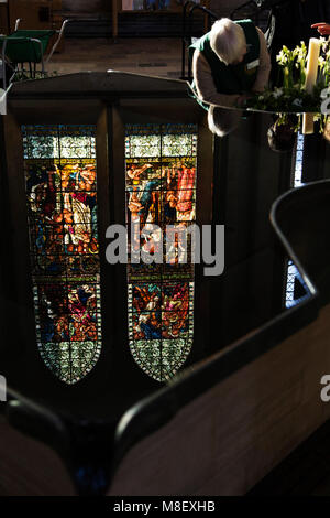 A woman arranges flowers at Salisbury Cathedral in Salisbury, Wiltshire, England. A stained glass window reflects - Stock Photo