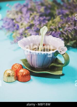 Handmade beautiful flower cup of fragrant tea violet porcelain and candies - Stock Photo