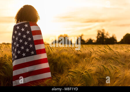 Mixed race African American girl teenager female young woman in a field of wheat or barley crops wrapped in USA - Stock Photo