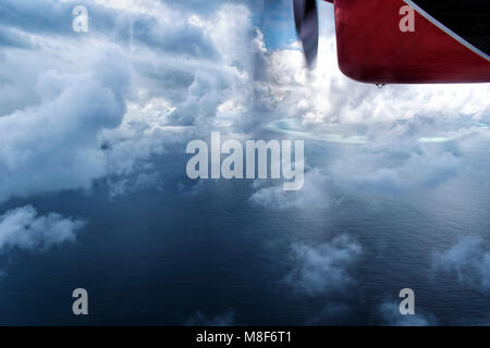 Aerial view from a seaplane flying through the clouds over Maldive island ocean sea for holiday background - Stock Photo