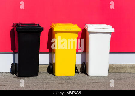 Three colored recycle bins on the street/ Black/ Yellow/ White - Stock Photo