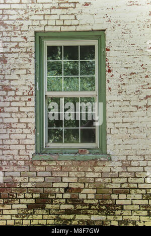Green framed pane glass window against weathered against white painted and red brick wall - Stock Photo