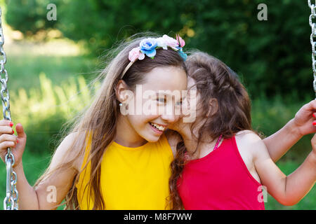 Two happy beautiful girls sitting on seesaw and talking at summer day - Stock Photo