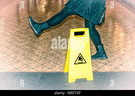 woman almost slips on a wet floor - Stock Photo