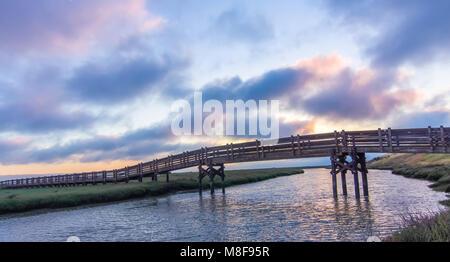 Sunset views of footbridge crossing salt evaporation pond in Don Edwards San Francisco Bay National Wildlife Refuge. - Stock Photo