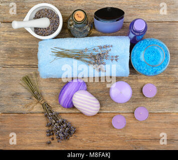 Goods for spa: soap, sea salt, towel, oil of lavender on wooden table. top view - Stock Photo