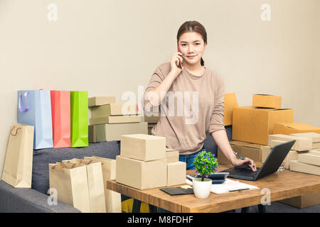 Young happy asian online seller, business woman, in her home talking to her customer on her phone while looking - Stock Photo