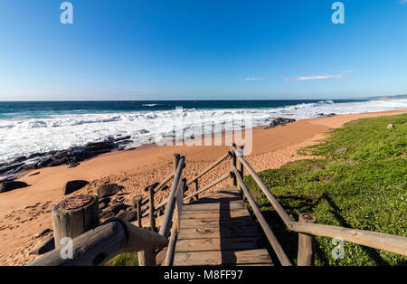 Seascape of empty wooden walkway leading onto rocky beach, waves and sea against blue coastal skyline in South Africa - Stock Photo
