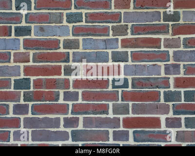 Colorful brick wall background featuring bricks with varying hues of red, green, gray, and blue, with a whimsical - Stock Photo