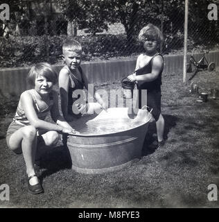 1940s, historical, three young children, a boy and two girls, having fun in a back garden playing by a oval shaped - Stock Photo