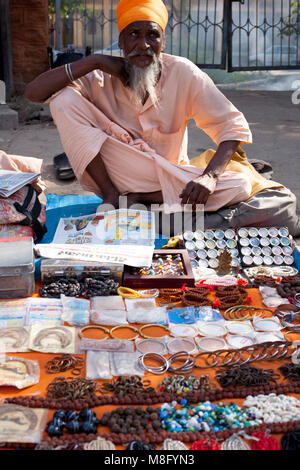 Indian sadhu - holy man sitting on pavement and selling jewelery and mala beads on streets of Jodhpur in India Rajasthan. - Stock Photo